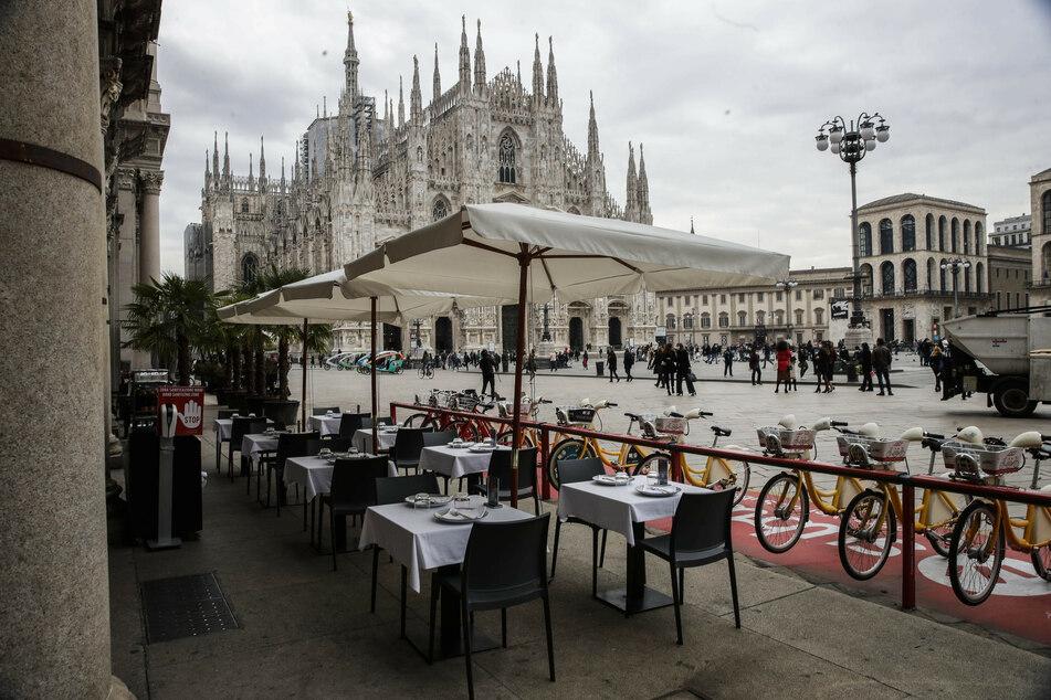 Die Terrasse eines Restaurants am Domplatz in Mailand ist menschenleer. Die italienische Region Lombardei hat wegen der stark steigenden Corona-Zahlen nächtliche Ausgangsverbote für die rund zehn Millionen Bürger erlassen.
