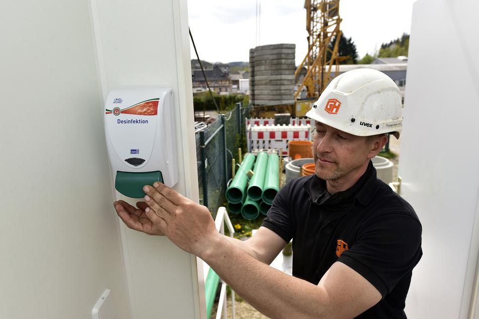 Dennis Paschke (43) desinfiziert an einem Container auf der Kläranlage-Baustelle in Grünhainichen regelmäßig seine Hände.