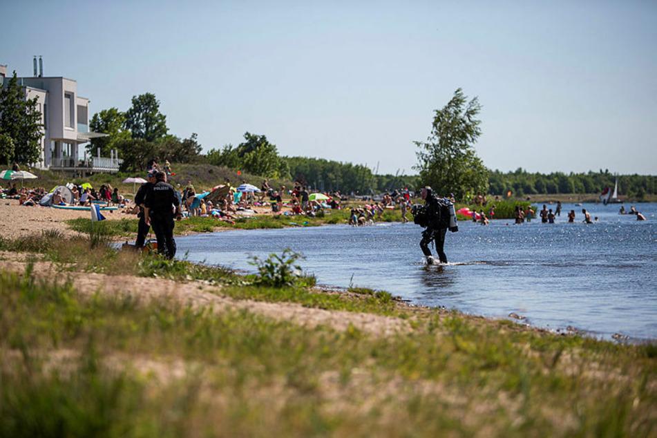 Vor Badegästen und Spaziergängern suchen Polizeitaucher am Ostufer des Cospudener Sees nach Hinweisen darauf, wie der junge Mann ums Leben kam.