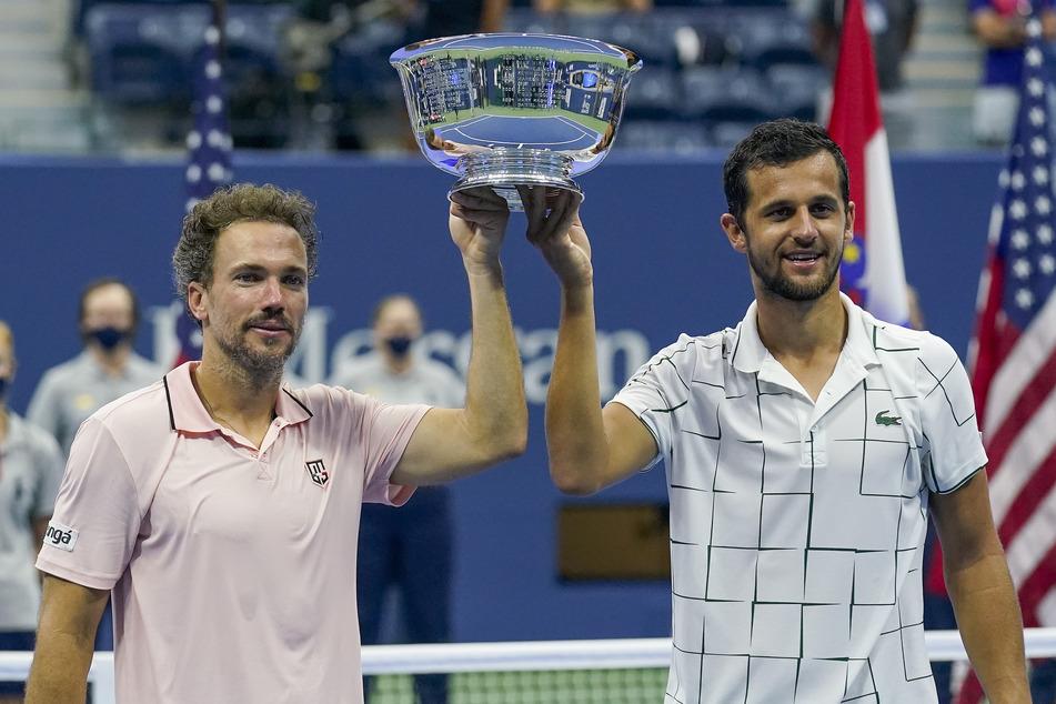 Bruno Soares (l) und Mate Pavic jubeln mit der Trophäe über ihren Sieg.
