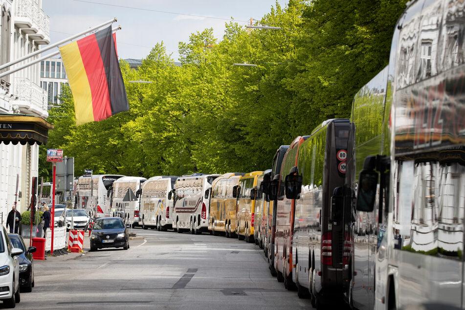 Zahlreiche Reisebusse nehmen an einem Buskorso um die Binnenalster teil.