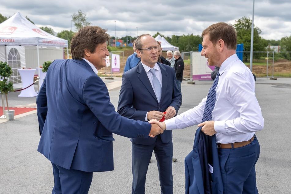 Der Norma-Vorstandsvorsitzende Gerd Köber (59, v.l.n.r.) und Niederlassungsleiter Matthias Lehmann (59) begrüßen Ministerpräsident Michael Kretschmer (46, CDU)