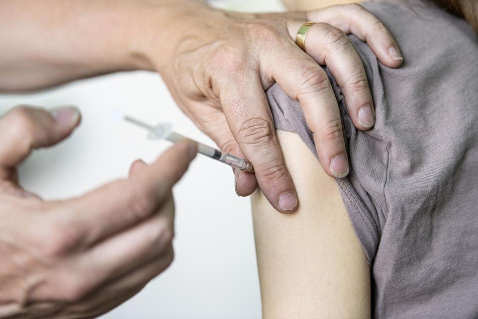 Ein Kinder- und Jugendarzt impft eine junge Frau mit dem Corona-Impfstoff von BioNTech/Pfizer.