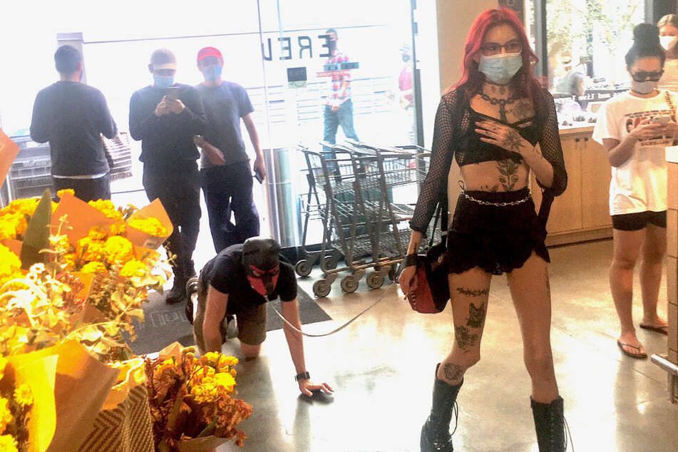 Unusual supermarket customer: A young dominatrix takes a man out shopping.
