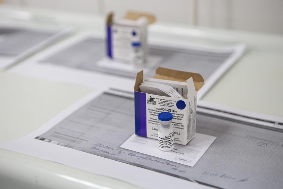 """Glasfläschchen gefüllt mit dem neuen russischen Corona-Impfstoff mit dem Namen """"Sputnik V"""" stehen während der klinischen Phase-3-Studien auf einem Tisch."""
