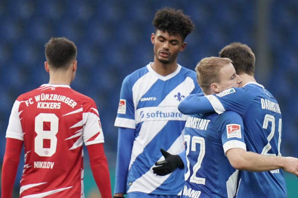 Darmstadts Immanuel Höhn (r-l), Fabian Holland und Tim Skarke jubeln nach dem 2:0, Würzburgs Vladimir Nikolov ist enttäuscht.