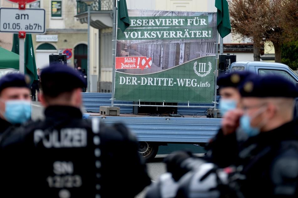 """Auf der Bühne einer Kundgebung der rechtsextremen Partei """"Der III. Weg"""" steht ein Plakat mit der Aufschrift """"Reserviert für Volksverräter!""""."""