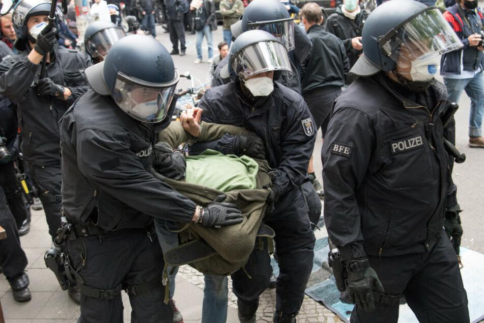 Polizisten führen einen Demonstranten während einer Kundgebung gegen die Corona-Einschränkungen auf der Rosa-Luxemburg-Straße ab.