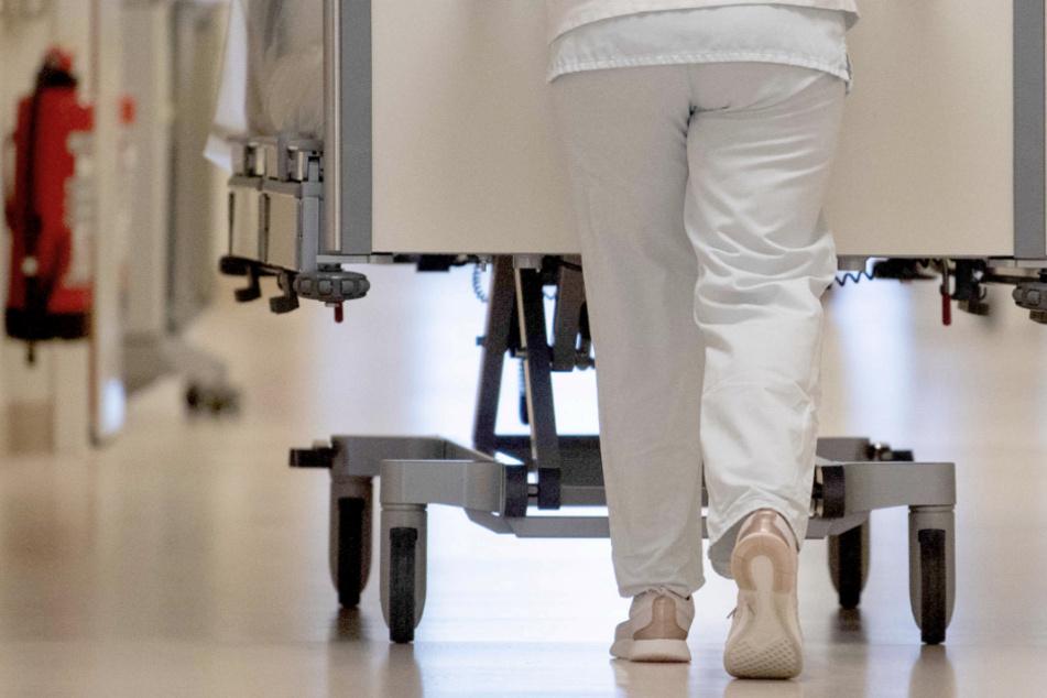 Eine Krankenpflegerin schiebt ein Krankenbett durch einen Flur. (Symbolbild)