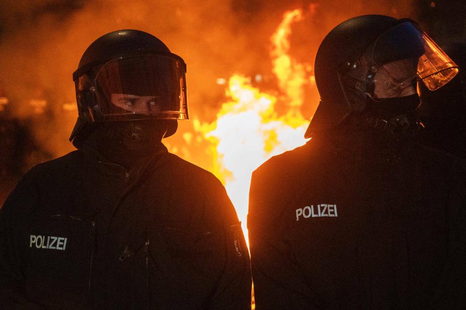 """Polizisten stehen vor einem Feuer am Rande des Demonstrationszugs linker und linksradikaler Gruppen unter dem Motto """"Demonstration zum revolutionären 1. Mai"""". Die Gewerkschaft der Polizei geht in diesem Zusammenhang von 50 verletzten Polizisten und über 250 Festnahmen aus."""