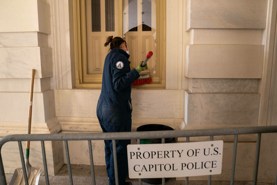 A U.S. Capitol employee cleans up glass from a broken window after Pro-Trump mobs breached the building.