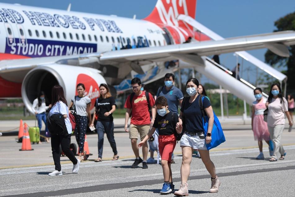 """Passagiere tragen Mundschutz am Malaysischen Flughafen """"Sultan Azlan Shah Airport""""."""