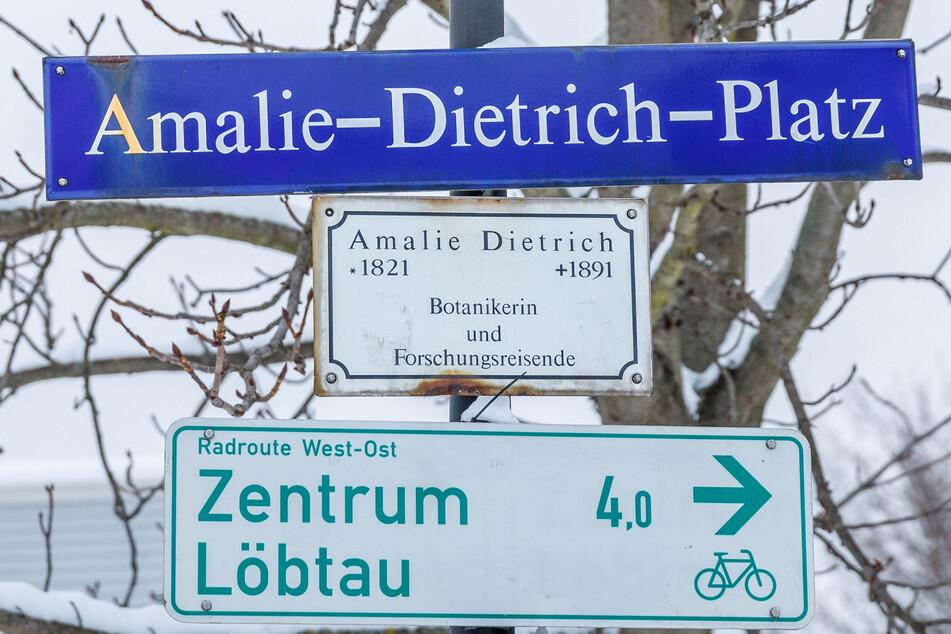 Unter dem Straßenschild erinnert eine Gedenktafel an das Werk der Forschungsreisenden.