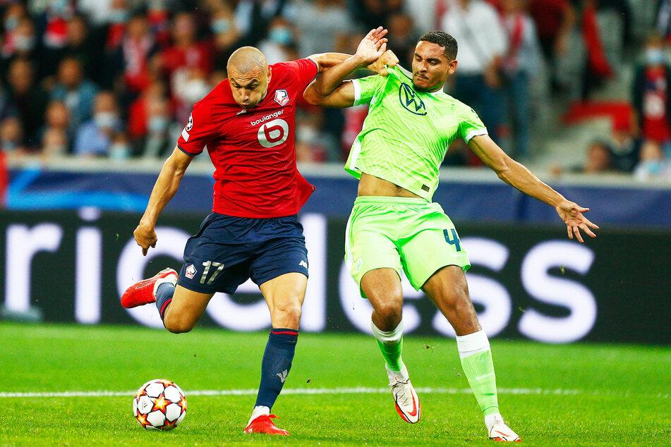 VfL Wolfsburgs Maxence Lacroix (r.) gegen Burak Yilmaz vom OSC Lille.
