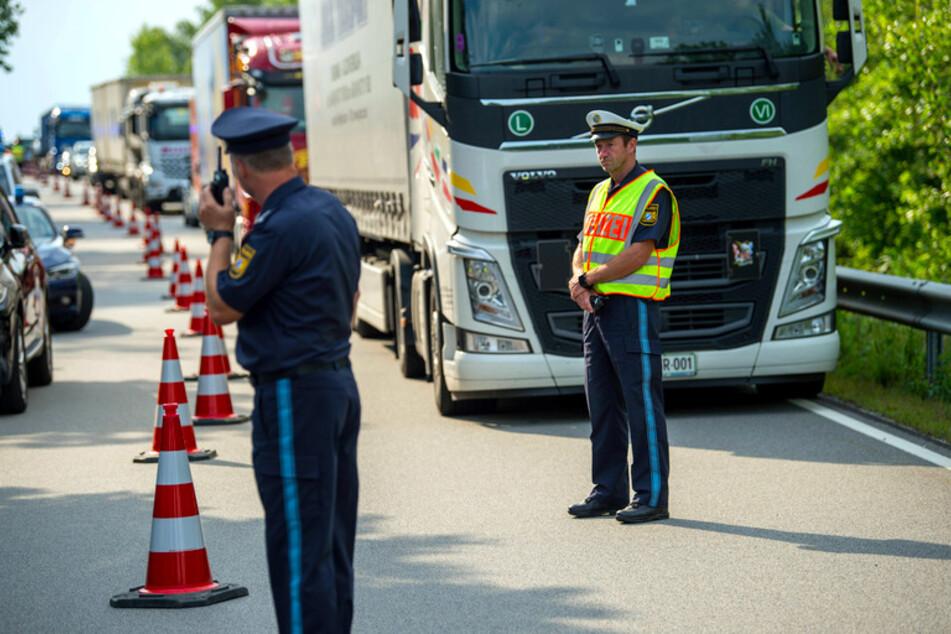 Ein Polizeibeamter stoppt zu Beginn der Grenzkontrollen durch die bayerische Landespolizei am Grenzübergang Kirchdorf den Verkehr.