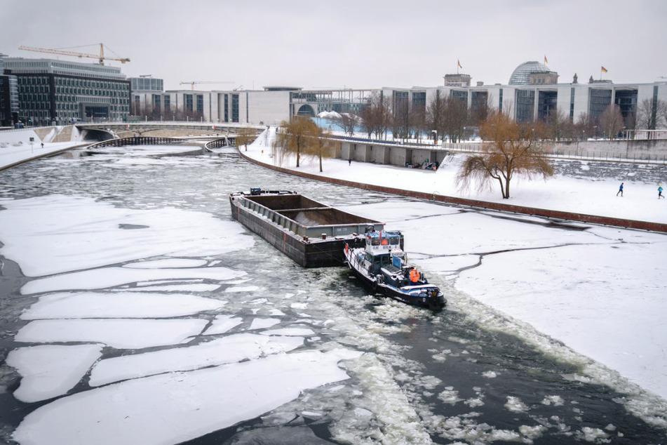 Ein Schubverband bahnt sich bei frostigen Temperaturen den Weg durch das Eis auf der Spree im Berliner Regierungsviertel. Auch in den kommenden Tagen bleibt es in der Hauptstadt eiskalt.