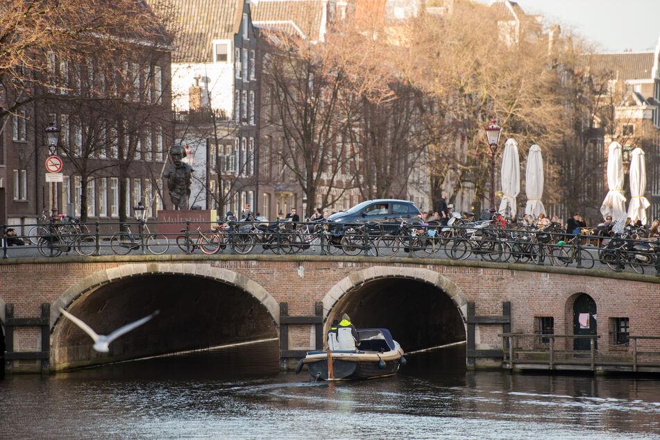 Ein Boot fährt auf einer Gracht unter einer Brücke in Amsterdam hindurch. Seit Anfang Juli stiegen die Infektionszahlen in der Niederlande um 500 Prozent innerhalb einer Woche.