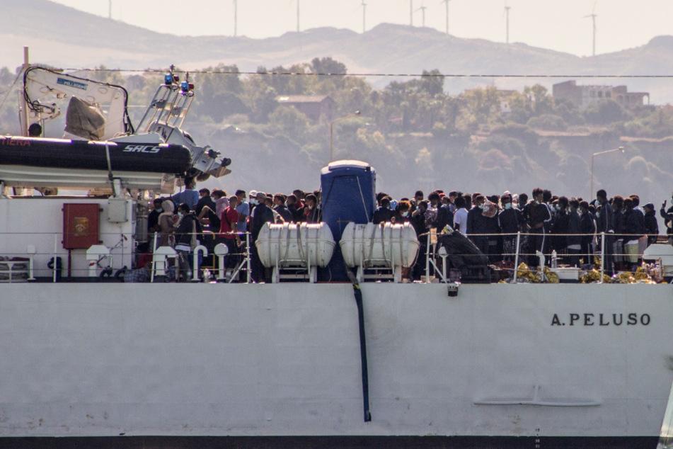 Migranten kommen an Bord von zwei Militärschiffen an.