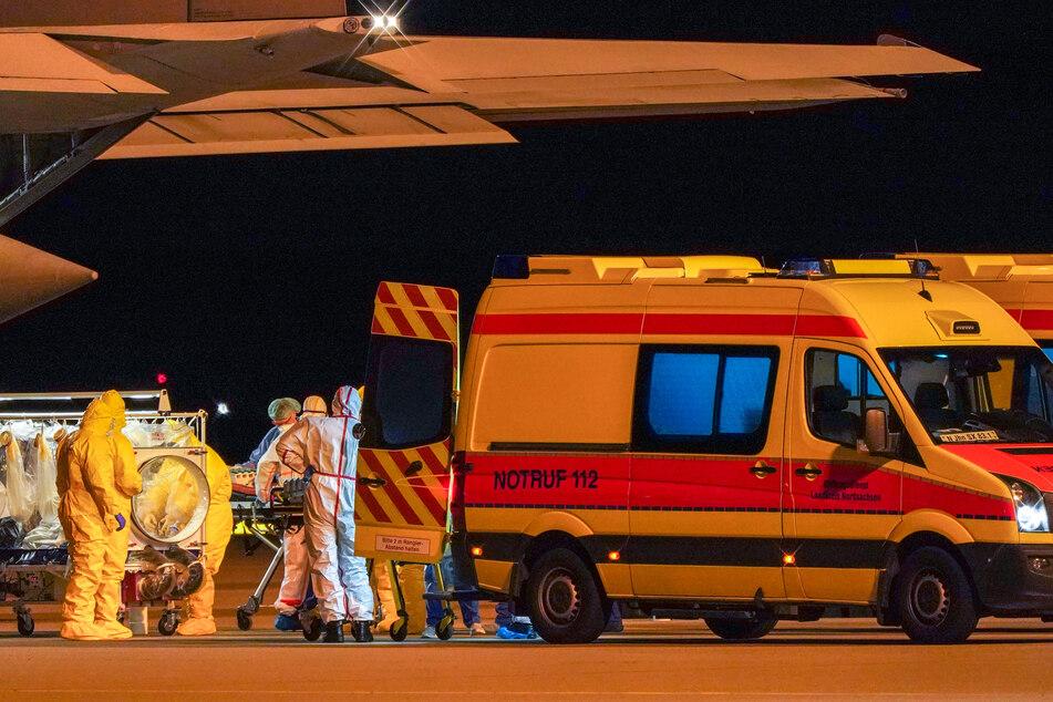 Ein Corona-Patient wird unter höchsten Schutzmaßnahmen am Leipziger Flughafen abtransportiert.