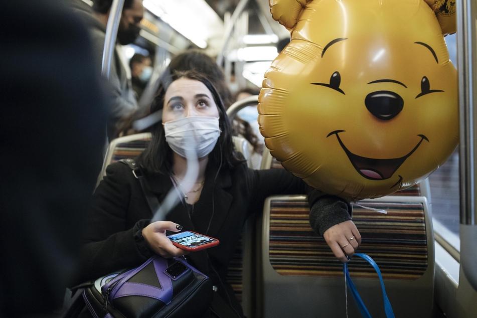 Paris: Eine Frau sitzt in der U-Bahn und hält einen Ballon von Pu der Bär. Um die Verbreitung des Coronavirus einzudämmen, sollen in Frankreich am 30. Oktober weitreichende Ausgangsbeschränkungen in Kraft treten.