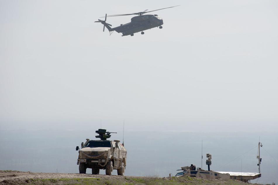 Ein Hubschrauber CH53 der Bundeswehr fliegt bei Masar-i-Scharif in Afghanistan über einen Dingo.