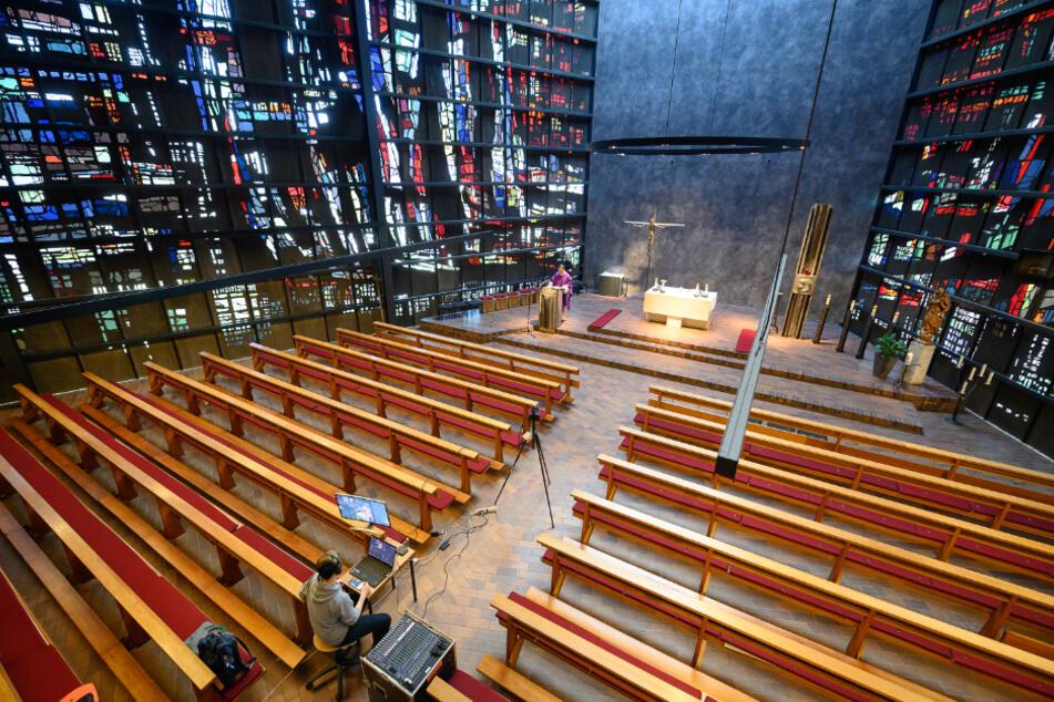 Winterbach: Pfarrvikar Patrick Stauß (hinten, links) leitet in einer leeren Kirche einen Gottesdienst der katholischen Kirchengemeinde Mariä Himmelfahrt, der auf YouTube gestreamt wird.
