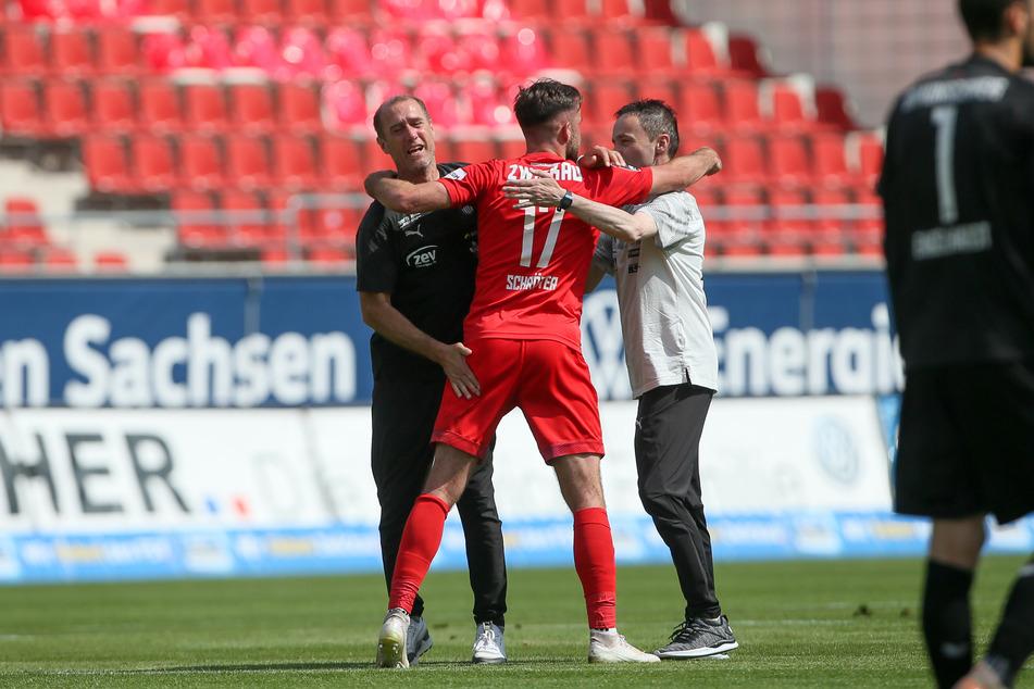 FSV-Coach Joe Enochs (l.) und Mannschaftsleiter Mario Kallisch (r.) umarmen Siegtorschütze Morris Schröter.