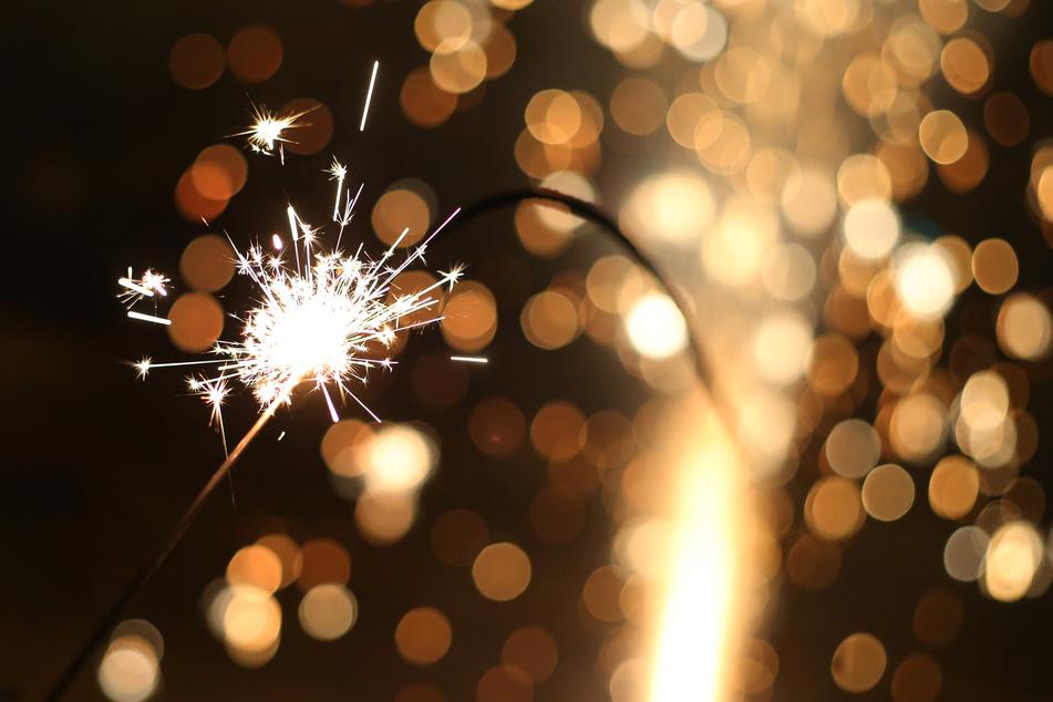 Eine große Wunderkerze brennt in der Silvesternacht.