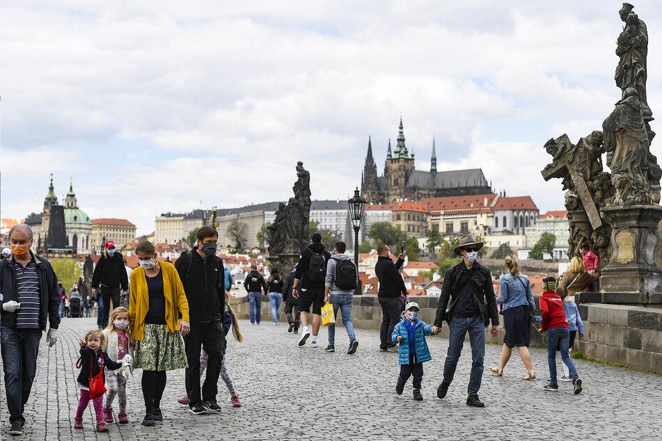 Menschen spazieren mit Mundschutz über die Karlsbrücke.