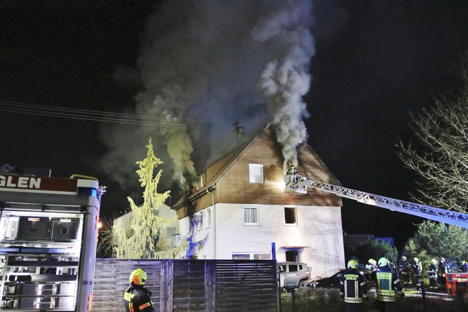 Feuerwehrleute löschen den Brand in einem Haus.