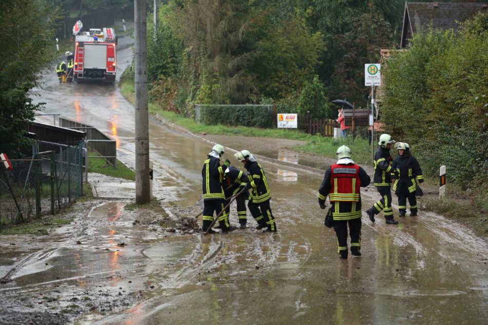 Feuerwehrleute befreien die Straße vom Schlamm.