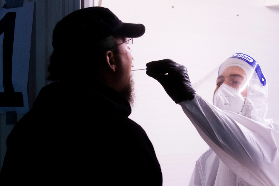 Ein Helfer der Johanniter nimmt im Corona Testzentrum am Flughafen Hannover einen Abstrich.