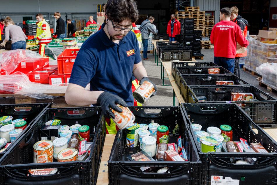 Ehrenamtliche Helfer der Hamburger Tafel und des Arbeiter-Samariter-Bunds packen im Zentraldepot Kisten mit Lebensmitteln.