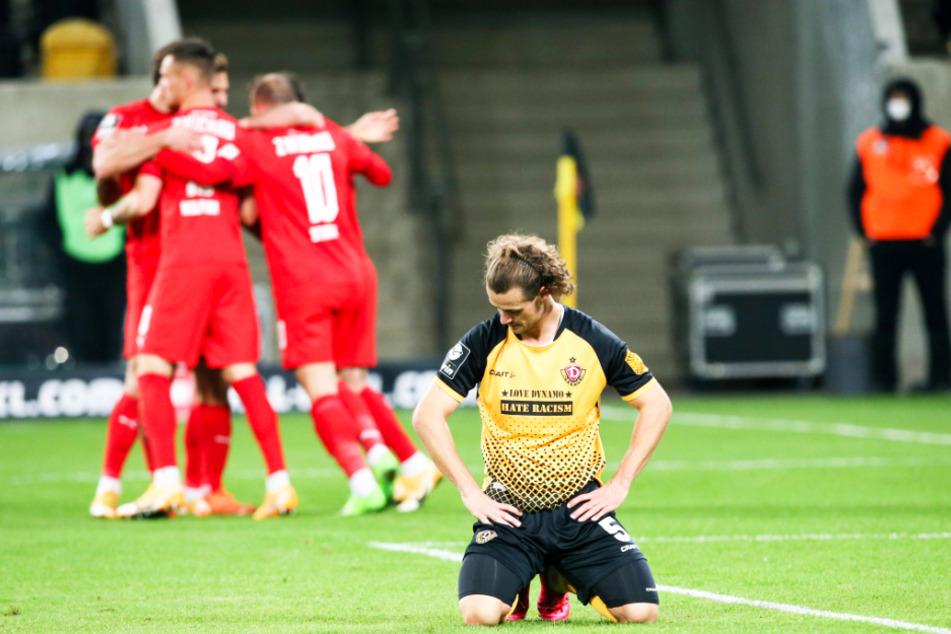 Während Dynamo-Kämpfer Yannick Stark (r.) auf dem Boden kniet, bejubeln die Spieler des FSV Zwickau ihr Tor.