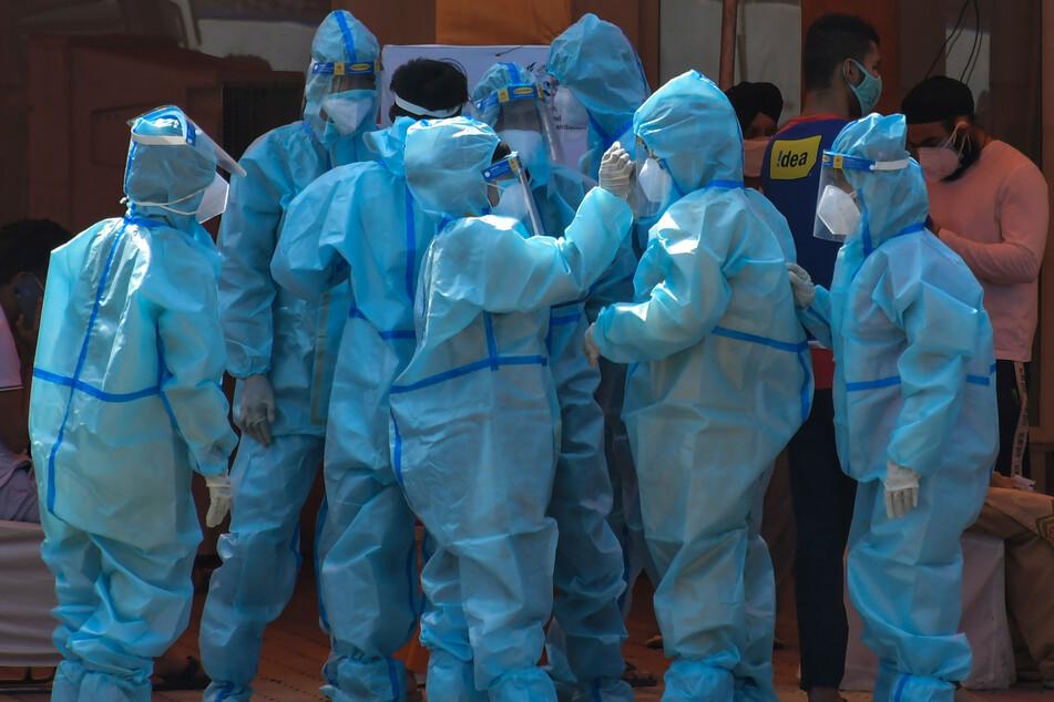 Neu-Delhi: Gesundheitspersonal und Freiwillige in Schutzanzügen warten vor einem speziell errichteten Corona-Krankenhaus.