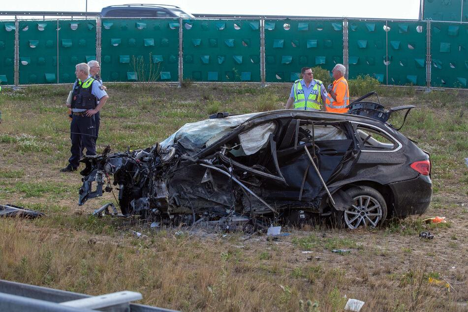 Einsatzkräfte stehen neben dem beschädigten Unfallfahrzeug.