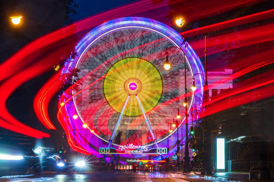 """Ein Riesenrad leuchtet am späten Abend auf dem Münchner Königsplatz vor der Kulisse der Propyläen, das dort für den """"Sommer in der Stadt"""" aufgebaut ist."""