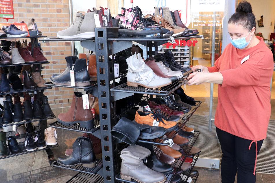 Für die Wiedereröffnung des Einzelhandels schiebt eine Verkäuferin Rollwagen mit Schuhen ins Freie.