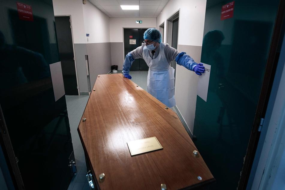 Ein medizinischer Mitarbeiter des Bichat-Claude-Bernard-Krankenhaus in Paris schiebt einen Sarg zur Vorbereitung in einen Trauerraum, damit sich die Familie von ihrem Angehörigen verabschieden kann.