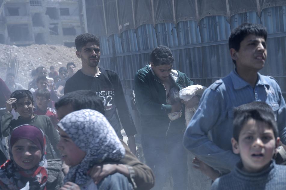 Syrien, Duma: Ein Jugendlicher steckt Brot in seine Tasche, nachdem Mitarbeiter der syrischen Regierung Nahrungsmittel an die Bewohner von Duma verteilten. (Archivbild)
