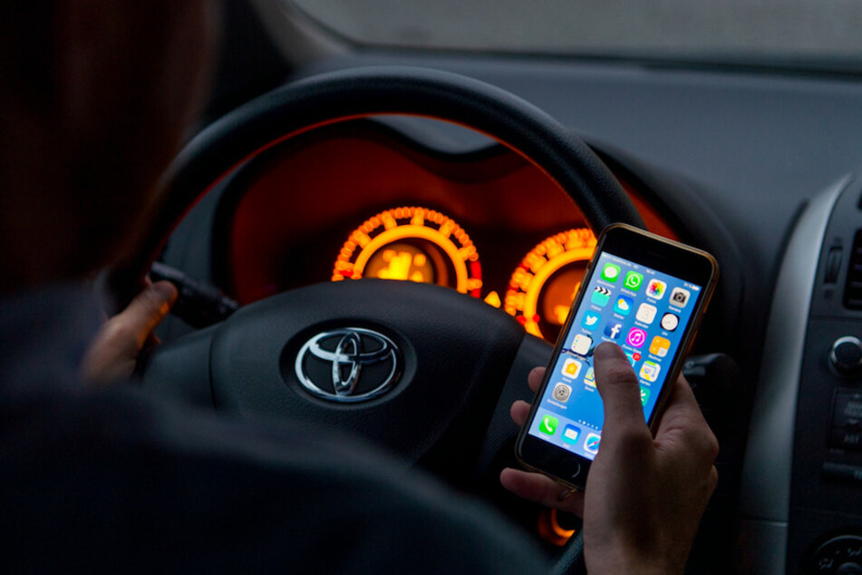 Wer am Steuer mit dem Smartphone hantiert muss mit Bußgeld, Punkt und Fahrverbot rechnen.
