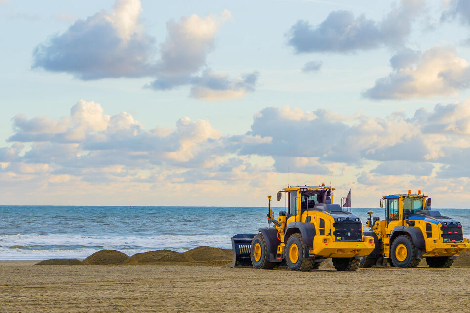 The tractor driver didn't see the sleeping woman as he was backing up on the beach.