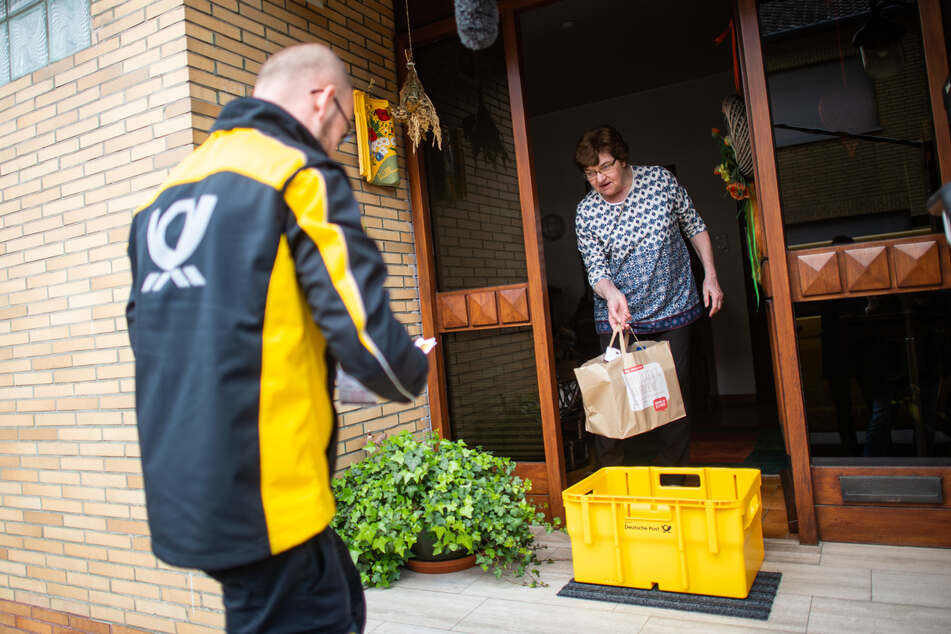 Michael Peltzer (l.), Postzusteller in Gangelt, trägt Lebensmittel in Postboxen zu einer Anwohnerin in Quarantäne.