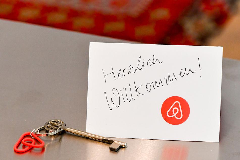 Ein Schlüssel mit einem Airbnb-Anhäger und eine Herzlich-Willkommen-Karte liegen in der Wohnung eines Airbnb-Gastgebers für den Gast bereit. (Symbolbild)