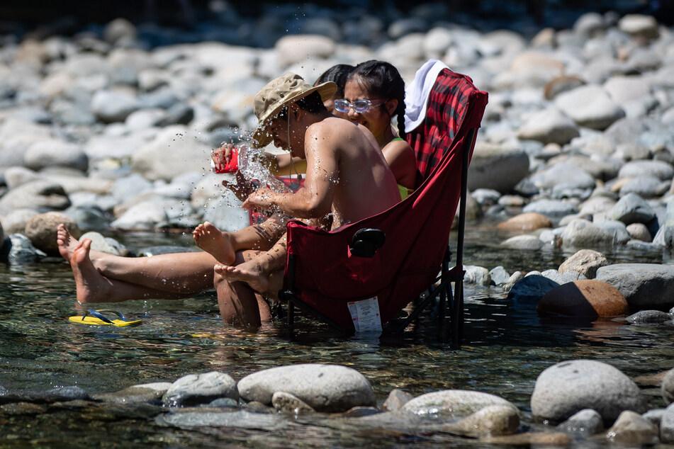 Drei Teenager kühlen sich im kalten Wasser des Lynn Creek ab. In einer Hitzewelle im Westen Kanadas haben die örtlichen Behörden die höchste Temperatur in der Geschichte des nordamerikanischen Landes gemessen.