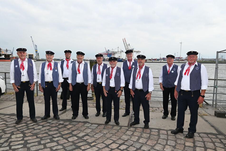 Zehn Shantys lächeln am Hamburger Hafen für die Kamera.