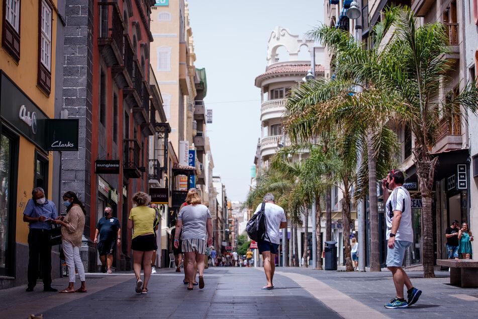 Spanien, Teneriffa: Menschen mit Masken gehen in Teneriffa eine Einkaufsstraße entlang.