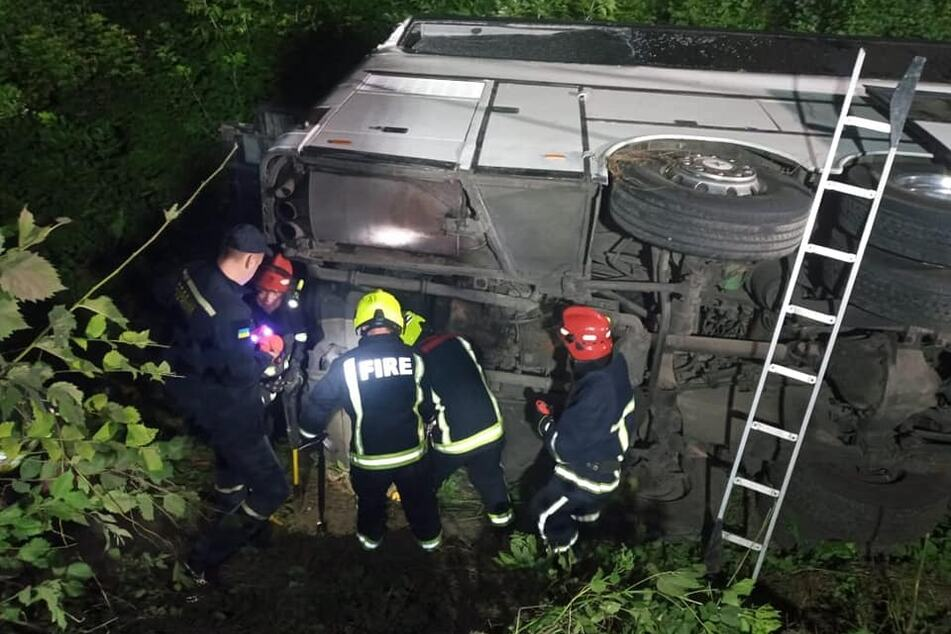 Einsatzkräfte begutachten den Bus, der in der Ukraine verunglückte.