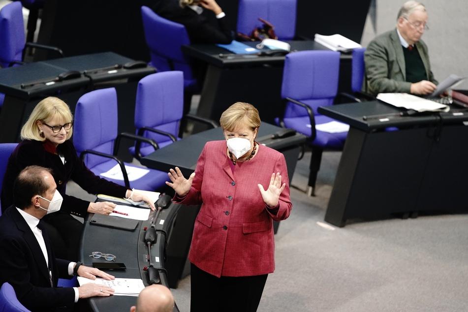 Bundeskanzlerin Angela Merkel (CDU) steht zu Beginn der Sitzung des Bundestags im Plenum mit einer Mund-Nasenbedeckung vor Abgeordneten der Fraktionen.