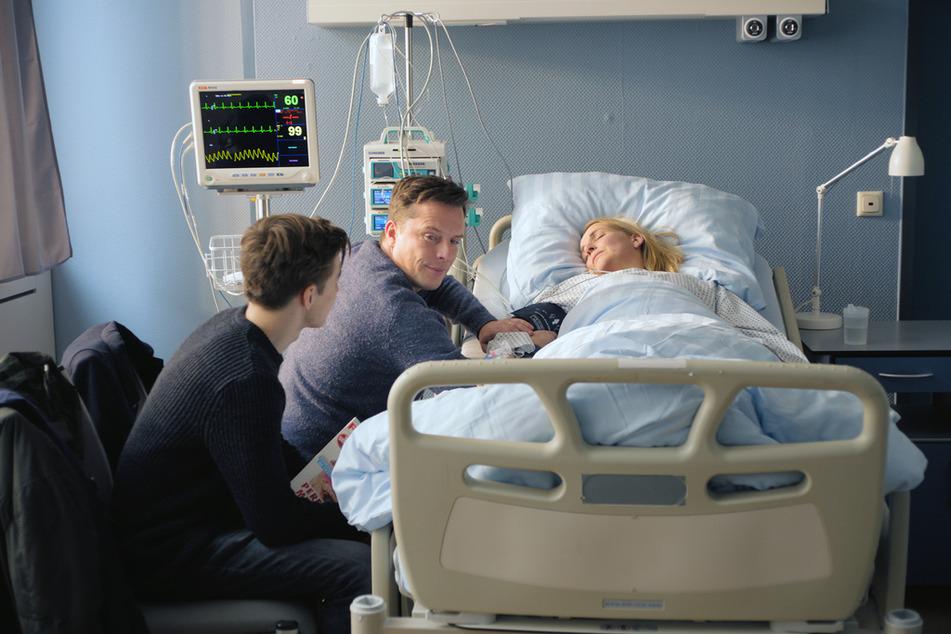 Flo (Nick Julius Schuck, l.) und Stefan (Florian Panzner, M.) warten ungeduldig darauf, dass Fritzie (Tanja Wedhorn, 49, r.) aus der Narkose erwacht. Sie wollen ihr die gute Nachricht überbringen, dass der Tumor entfernt werden konnte.